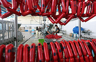 epa04167247 Afghan men fill meat into sausages at a sausage factory in Herat, Afghanistan, 14 April 2014. According to local information the factory produces around 4 tonnes of sausages daily, which are mostly consumed in Herat city. The factory's owners were planning to enhance the production to be able to sent their products also to other provinces of the war-torn country, they said.  EPA/JALIL REZAYEE